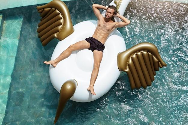 Wysoki kąt widzenia spokojnego mężczyzny bez koszuli w majtkach do pływania relaksującego się na nadmuchiwanej tratwie w basenie, trzymającego ręce za głową i mającego zamknięte oczy podczas letnich wakacji w gorącym kraju