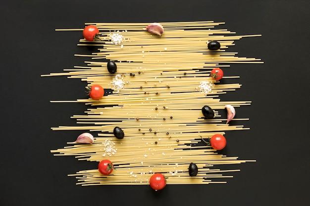 Wysoki kąt widzenia surowego makaronu spaghetti; pomidor wiśniowy; czarna oliwka i czarny pieprz ułożone na czarnej powierzchni