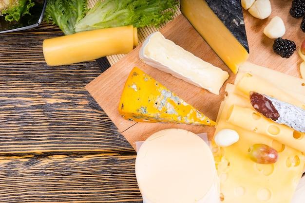 Wysoki kąt widzenia talerza serów z różnymi serami na płycie z miejscem na kopię na rustykalnym drewnianym stole