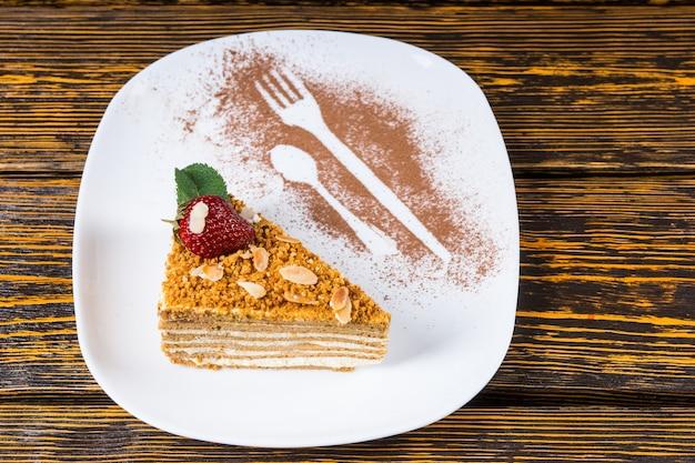 Wysoki kąt widzenia trójkątnego klina warstwowego ciasta orzechowego przyozdobionego truskawkami i miętą podanego na białym talerzu z naczyniami posypanymi kakao na powierzchni drewnianego stołu