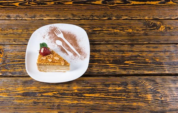 Wysoki kąt widzenia trójkątnego klina warstwowego ciasta przyozdobionego truskawkami i miętą podawanego na białym talerzu z naczyniami posypanymi kakao na drewnianej powierzchni stołu z miejscem na kopię