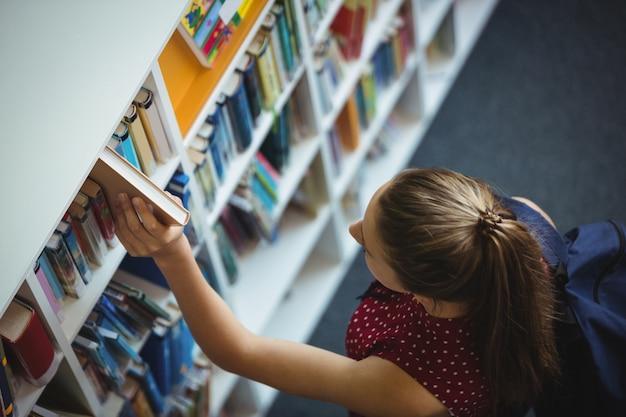 Wysoki kąt widzenia uczennicy wybierając książkę z półki w bibliotece