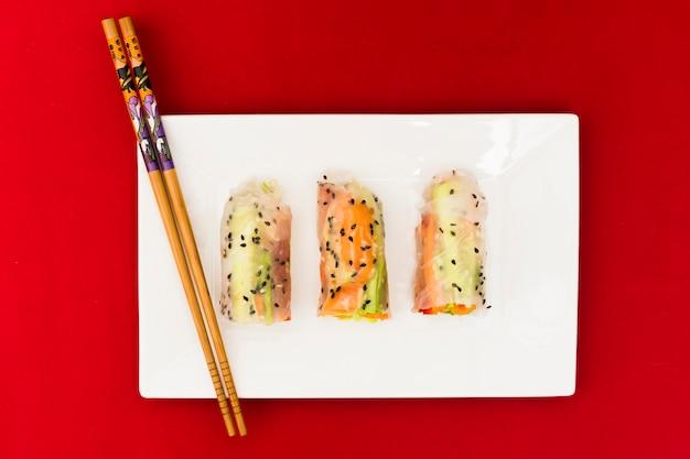 Wysoki kąt widzenia warzyw sajgonki ryżowe ozdobione sezamem na białym talerzu z drewnianymi pałeczkami