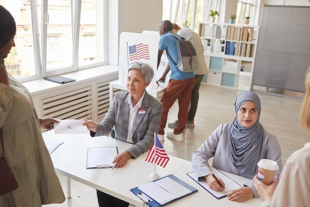 Wysoki kąt widzenia wieloetnicznej grupy ludzi rejestrujących się do głosowania w lokalu wyborczym ozdobionym amerykańskimi flagami, miejsce na kopię