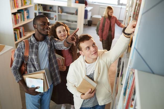 Wysoki kąt widzenia wieloetnicznej grupy uczniów zdejmujących książki z półki w szkolnej bibliotece,