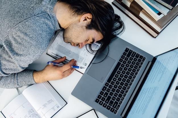 Wysoki kąt widzenia zmęczony biznesmen śpi podczas obliczania wydatków przy biurku w biurze. młody mężczyzna kaukaski pracownik uciąć sobie drzemkę w biurze na stole z tabletu i laptopa.
