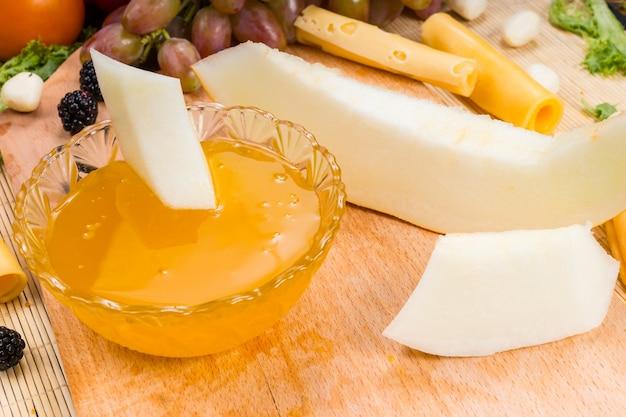 Wysoki kąt z bliska widok wykwintnych serów i deski z owocami z miską z przetworami owocowymi do maczania