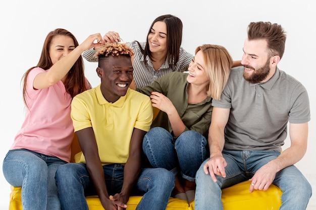 Wysoki kąt zabawy młodych przyjaciół na kanapie