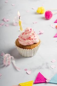 Wysoki kąt zapalonej świeczki w urodziny cupcake