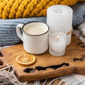 Wysoki kąt zapalonych świec ze swetrem i filiżanką kawy