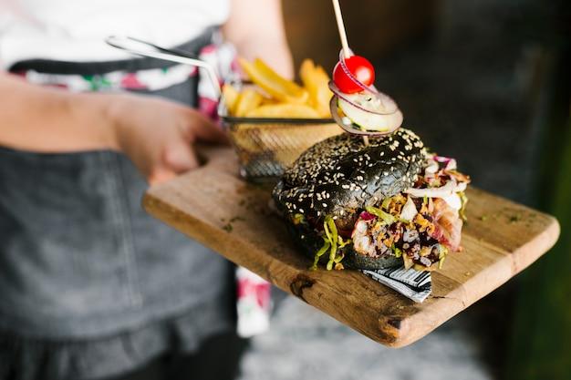 Wysoki kąt zbliżenie kelner gospodarstwa drewnianą deskę z czarnym burger i frytki