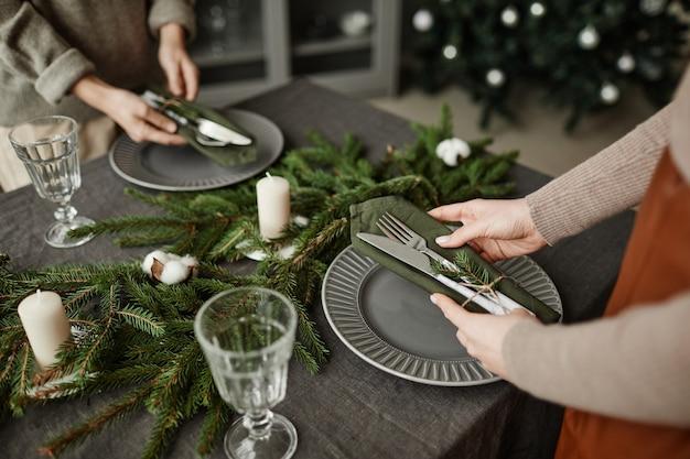 Wysoki kąt zbliżenie młodej kobiety ustawiającej talerze na stole udekorowanym na boże narodzenie z fi...