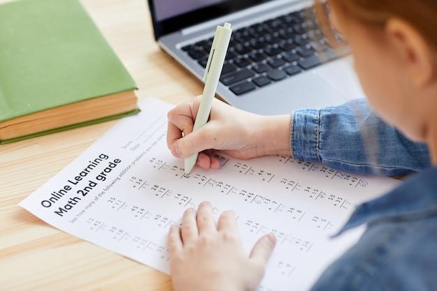 Wysoki kąt zbliżenie nierozpoznawalnej małej dziewczynki wykonującej test z matematyki lub pracę domową do szkoły online podczas nauki w domu, skopiuj miejsce