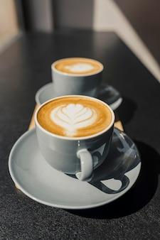 Wysoki kąt zdobionych filiżanek kawy wykonany przez baristę