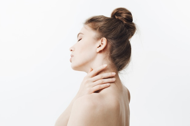 Wysoki klucz. oszałamiająca przystojna kaukaska młoda kobieta z ciemnymi długimi włosami w kokowej fryzurze, trzymająca szyję rękami, obracająca głowę ze zmęczonym wyrazem twarzy i zamkniętymi oczami. dziewczyna cierpi na ból szyi.