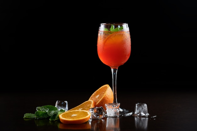 Wysoki kryształowy kieliszek koktajlowy z zimnym letnim orzeźwiającym soczystym napojem, plasterkami pomarańczy, świeżymi zielonymi liśćmi mięty i przezroczystymi kostkami lodu na głębokiej czerni