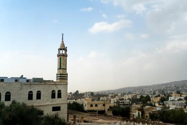 Wysoki minaret przy muzułmańskim meczecie na tle błękitnego nieba i miasta na wzgórzu. bliski wschód. jordania. jerash.