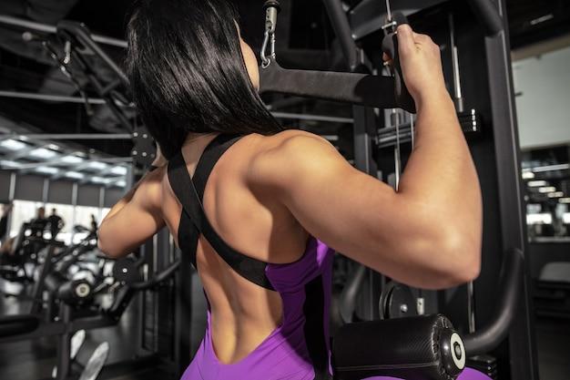 Wysoki. młoda muskularna kobieta kaukaski ćwiczenia w siłowni ze sprzętem. atletyczna modelka robi ćwiczenia prędkości, trenuje ręce i klatkę piersiową, górną część ciała. wellness, zdrowy styl życia, kulturystyka.