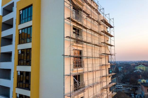 Wysoki niedokończony budynek mieszkalny lub biurowy w budowie. ściana z cegieł w rusztowaniu, błyszczące okna i wieżowiec na tle krajobrazu miejskiego i niebieskiego nieba. fotografia lotnicza dronów.