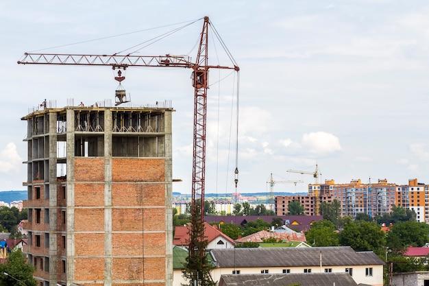 Wysoki piętrowy budynek w budowie z dźwigiem wieżowym i robotnikami