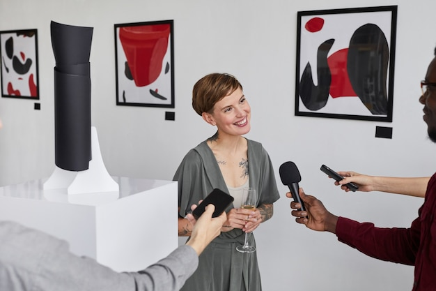 Wysoki portret eleganckiej wytatuowanej kobiety udzielającej wywiadu dziennikarzom podczas otwarcia wystawy w galerii sztuki współczesnej