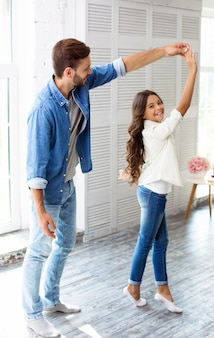Wysoki przystojny ojciec tańczy ze swoją uroczą nastoletnią córką w ich wielkim, jasnym salonie, śmiejąc się i bawiąc razem