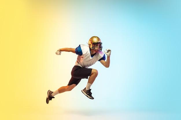 Wysoki skok. amerykański piłkarz odizolowany na gradiencie w świetle neonowym