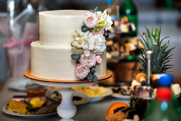 Wysoki słodki tort weselny ozdobiony żywymi różowymi i białymi kwiatami na stole