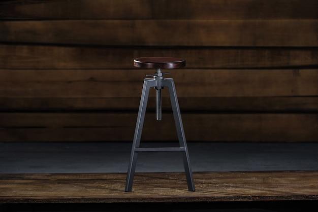 Wysoki stołek barowy na drewnianym tle