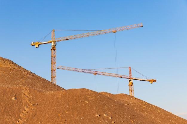 Wysoki stos piasku i grupy żurawi wieżowych na dużej wysokości na placu budowy, powierzchnia nieba słońca. przyszły kompleks mieszkalny.