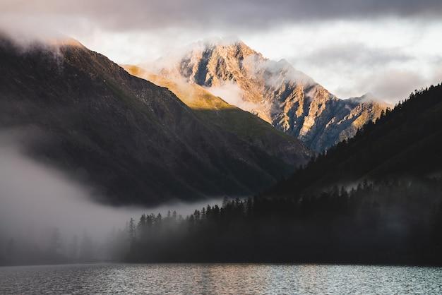 Wysoki szczyt górski złota i wiele niskich chmur nad jeziorem górskim o wschodzie słońca. gęsta mgła nad wodą i lasem w złotej godzinie. atmosferyczny góralski krajobraz wczesnym rankiem. alpejska relaksująca sceneria.