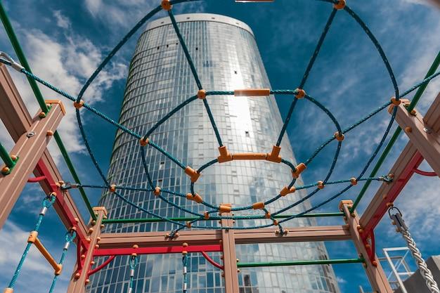 Wysoki szklany budynek przez wielokolorowy plac zabaw dla dzieci