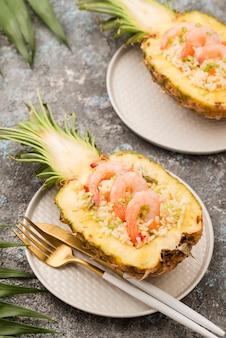 Wysoki widok ananasa na talerzu ze sztućcami