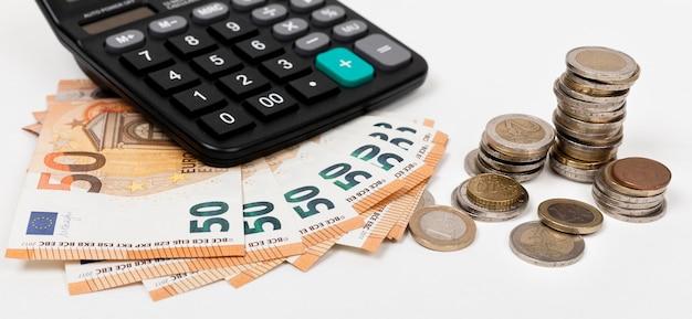 Wysoki widok banknotów i monet z kalkulatorem