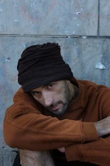 Wysoki widok bezdomnego w brudnych ubraniach