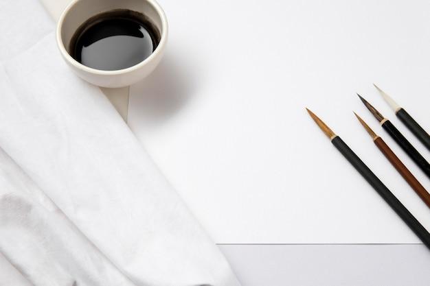 Wysoki widok biały papier z tuszem i pędzlami