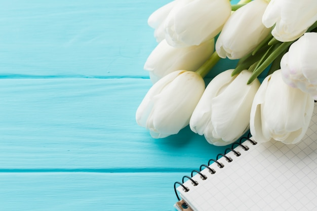 Wysoki widok bukiet kwiatów tulipanów i notatnik