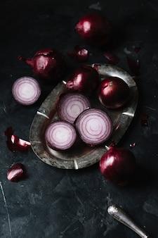 Wysoki widok czerwone cebule na talerzu i nożu