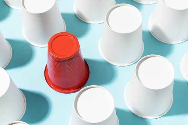 Wysoki widok czerwony plastikowy kubek otoczony papierowymi kubkami