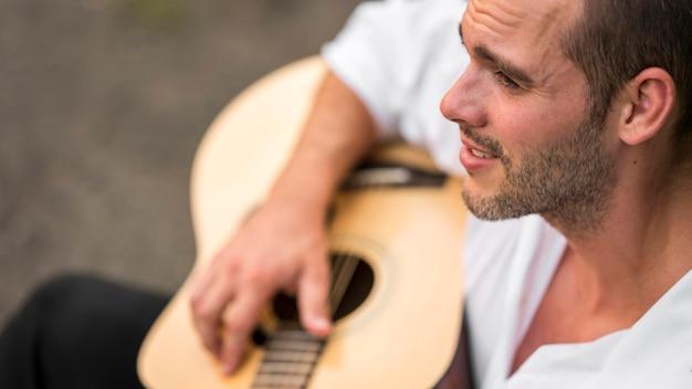 Wysoki widok człowieka grającego na gitarze w przyrodzie