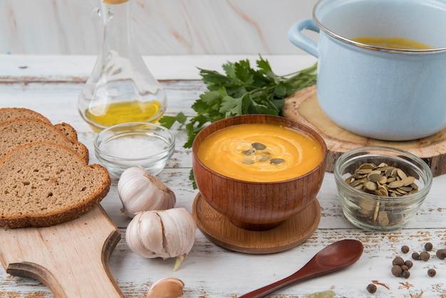 Wysoki widok drewniany stół z zupą i kromkami chleba