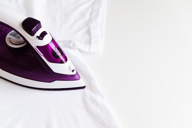 Wysoki widok fioletowy żelazo z białym tłem