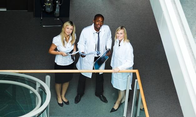 Wysoki widok grupa lekarki stoi w szpitalu