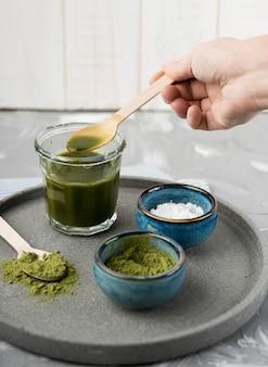 Wysoki widok herbaty matcha w szkle z ziołami w miskach