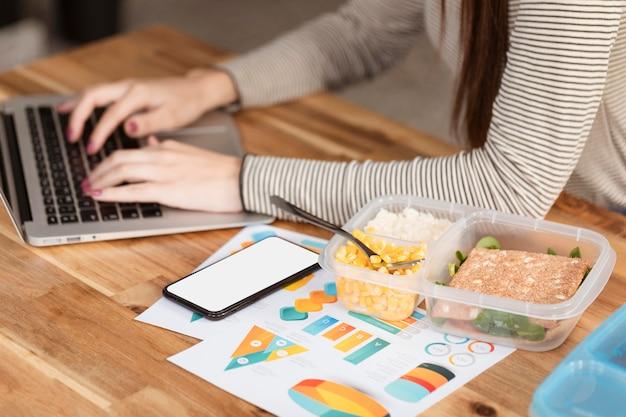 Wysoki widok kobieta pracuje i lunch pudełka