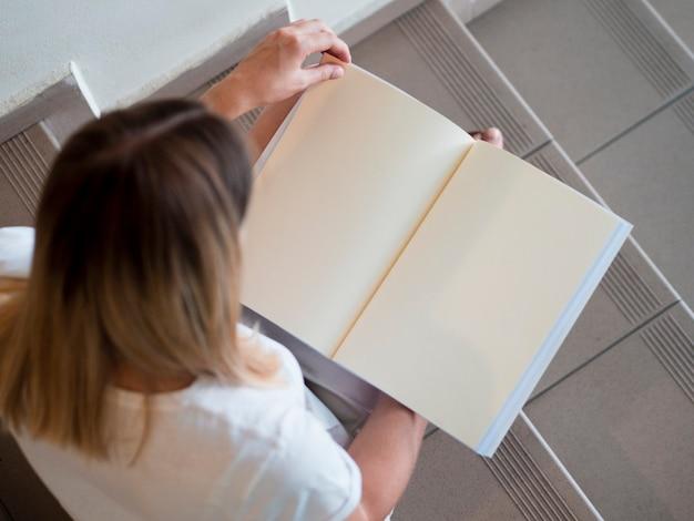 Wysoki widok kobieta trzyma próbnego magazyn