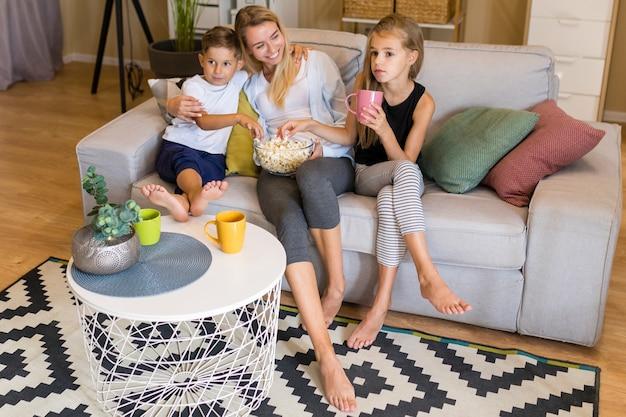 Wysoki widok kobiety i dzieci jeść popcorn