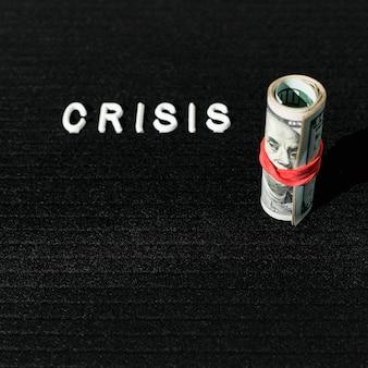 Wysoki widok kryzysu słowo i rolka banknoty