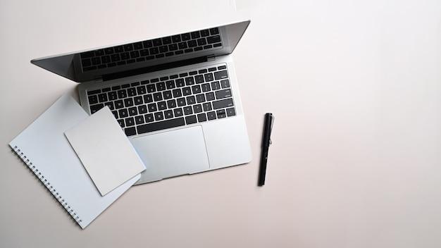 Wysoki widok laptopa, notebooka i pióra na białym stole.