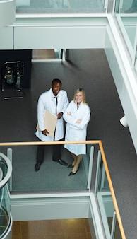 Wysoki widok męski i żeński lekarki ono uśmiecha się przy kamerą